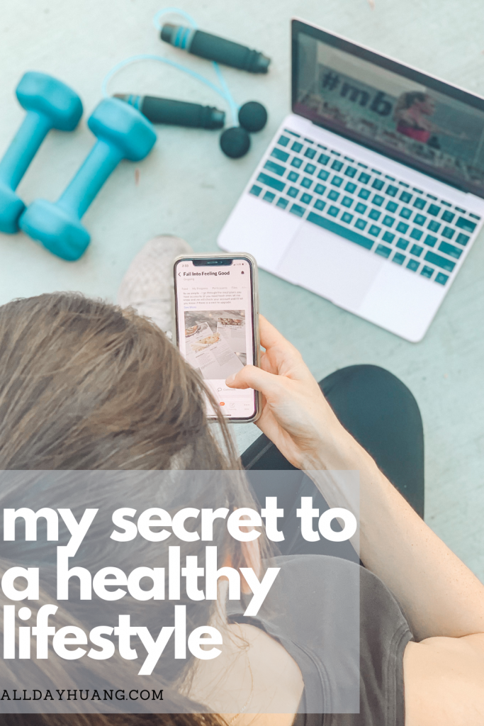 Fitness girl watching phone with laptop and dumbbells in the background.