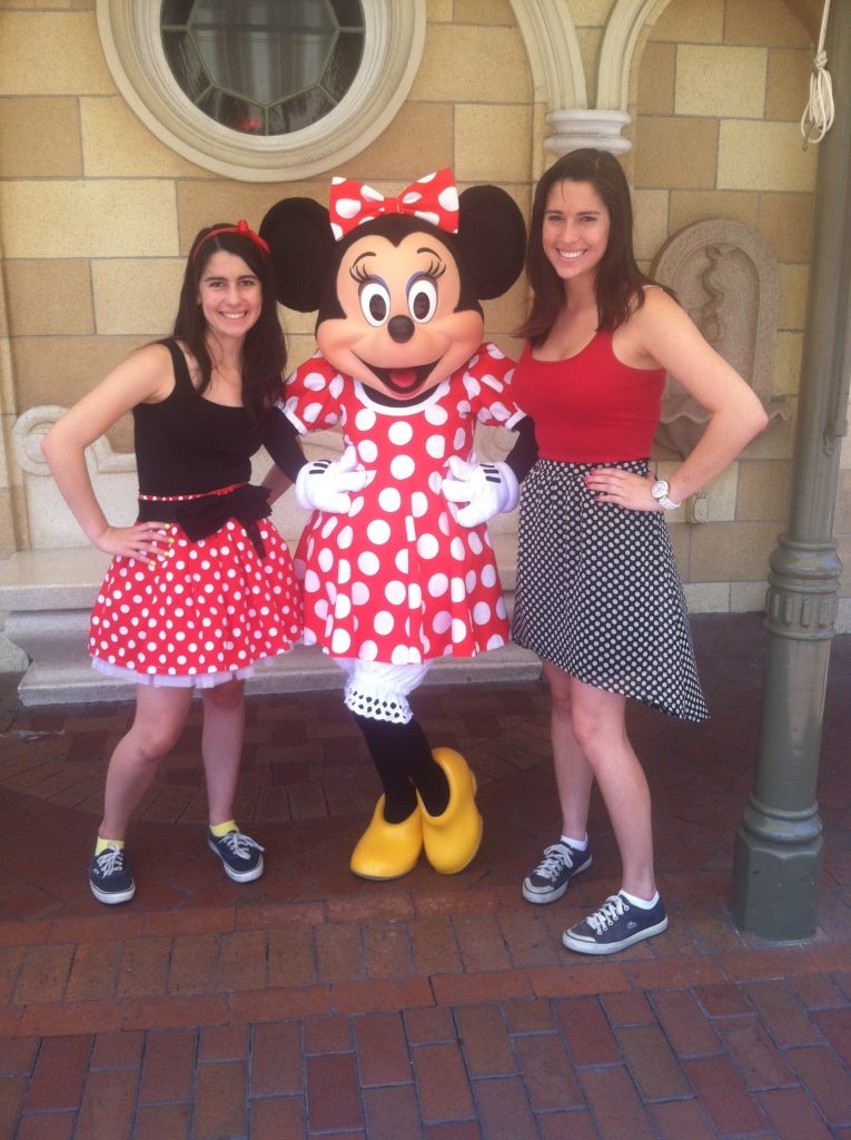 2 girls in polka dot skirts with a live character of Mini Mouse