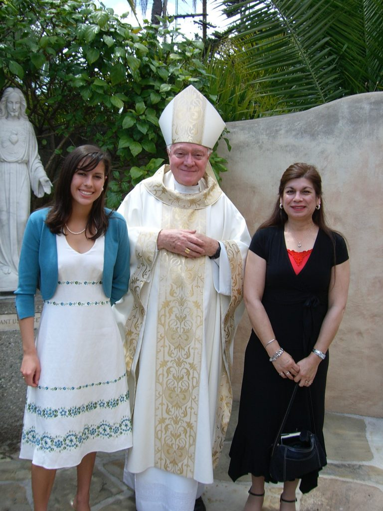 A girl and woman with a Catholic bishop