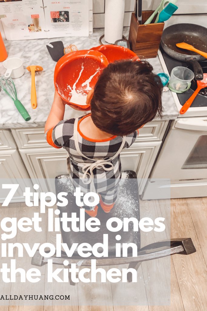 A toddler with an apron helping out in the kitchen while standing on a chair