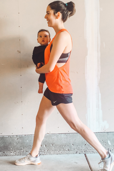 Woman in workout clothing holding a baby.